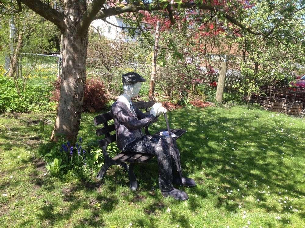 Wetterfest für die nächsten Jahr sitzt er auf seiner Gartenbank