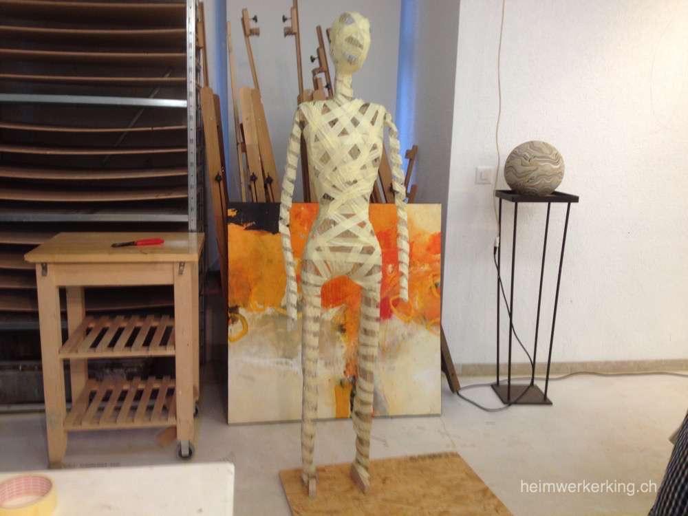 Stehende Figuren werden mit den Füssen auf ein Brett montiert